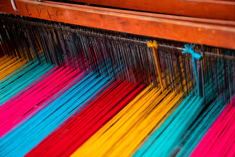 Strands of colorful yarn in a loom